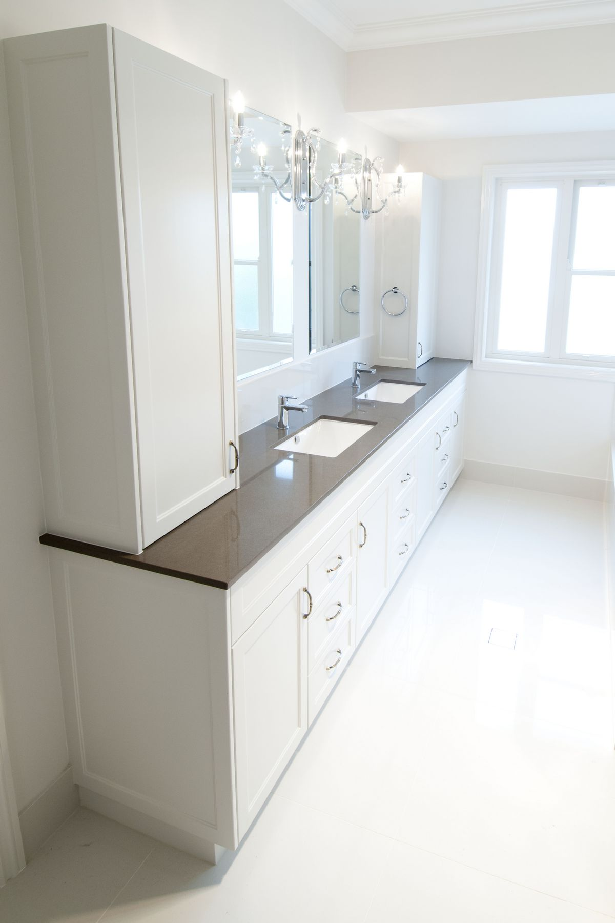 Traditional style vanity with double basin _ wall cabinetry on either side of vanity for ample storage