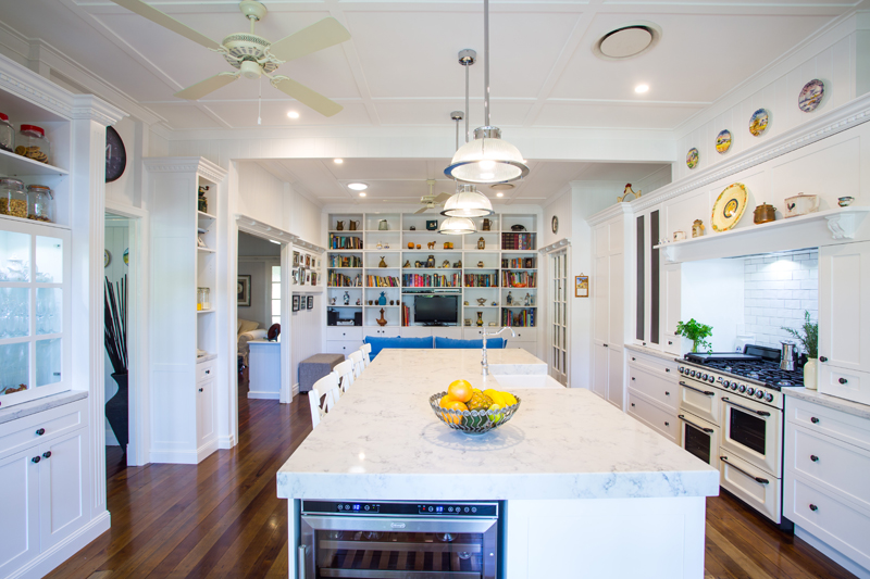 The kitchen complements the custom built cabinetry with shelving and dental mould capping flows throughout the room