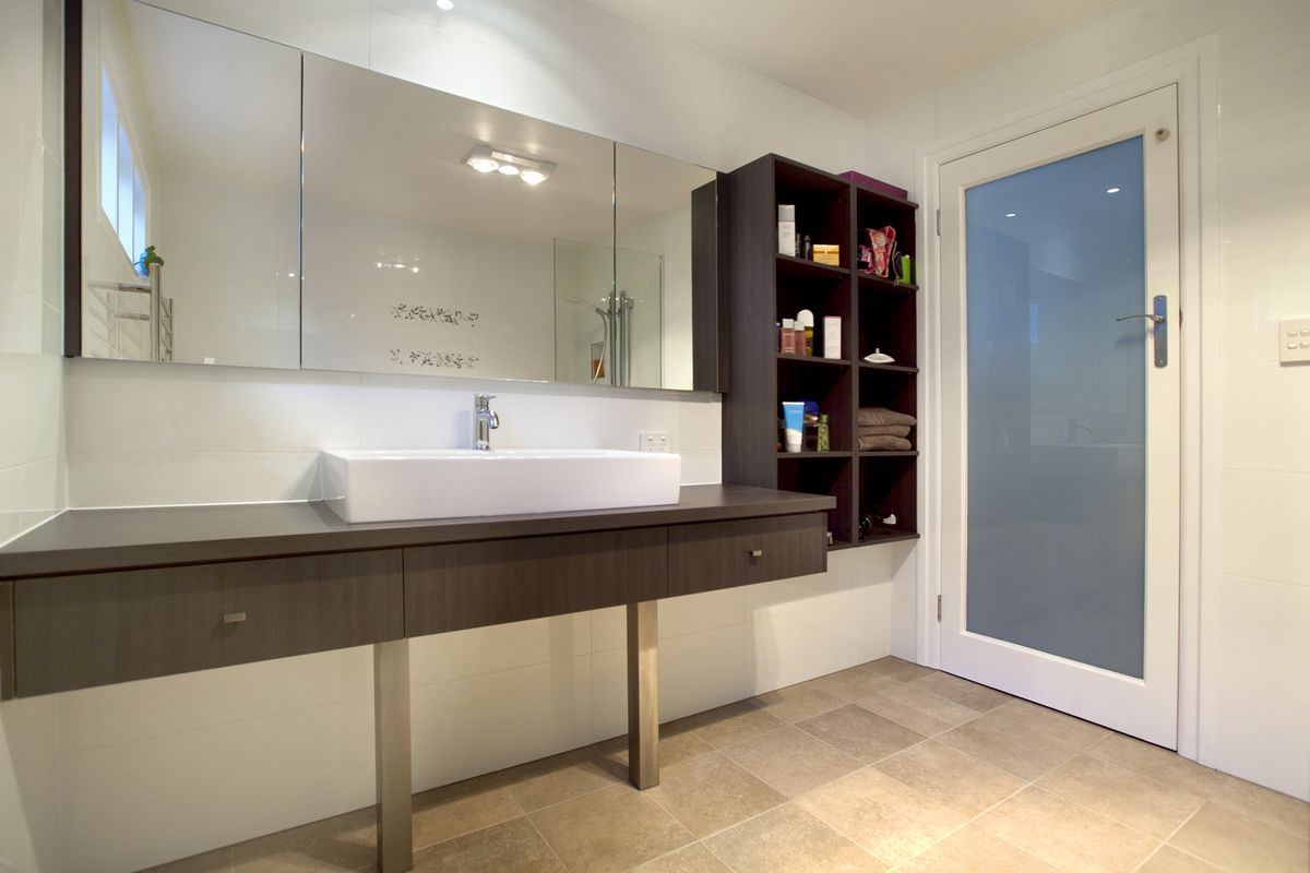 Bathroom with plenty of storage under basin, in mirrored cabinet and shelving on wall