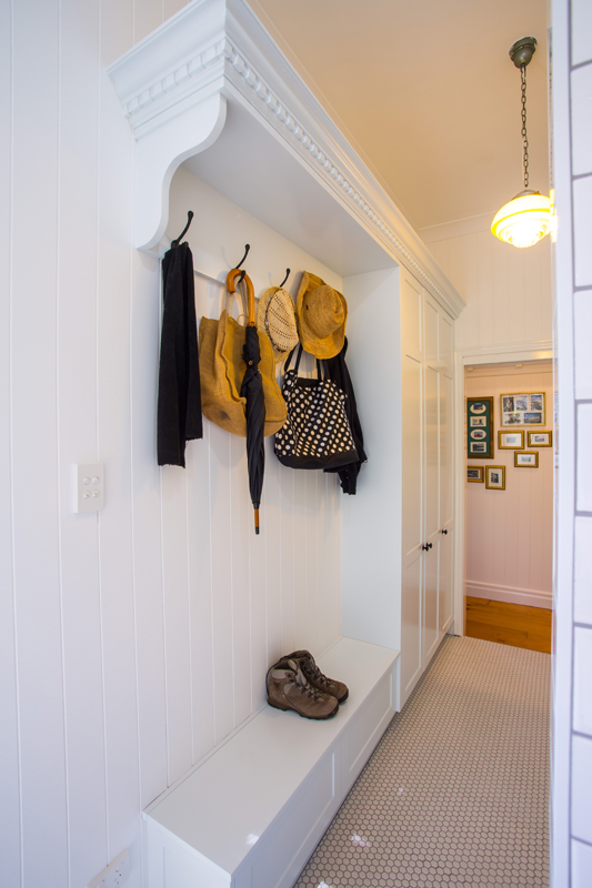 Laundry encompasses a hat _ coat stand and storage in the bench seat below