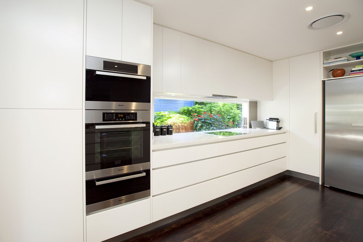 Sleek large drawers and wall cabinetry built to the ceiling to maximise storage with a garden view