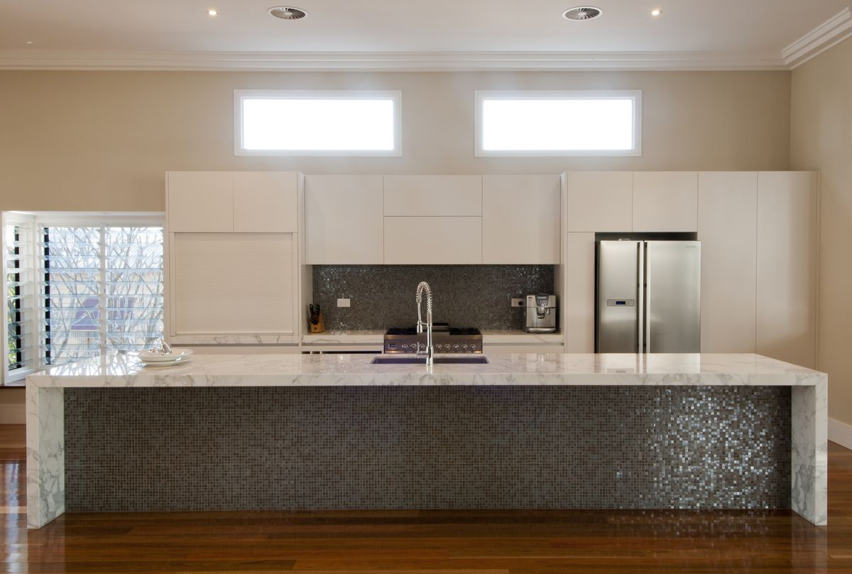 This stunning contemporary kitchen features  Carrara Marble island bench